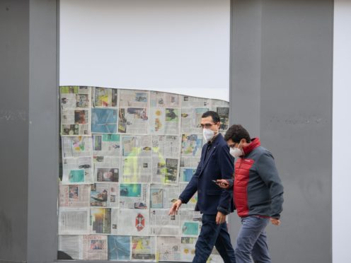 Men wearing protective face masks pass a closed-down shop on Oxford Street in London (Dominic Lipinski/PA)
