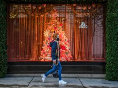 A woman wearing a face mask passes a Christmas window display on Oxford Street, London (Kirsty O'Connor/PA)