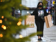 A woman wearing a face mask carrying shopping bags passes Christmas lights outside shops on Oxford Street, London (Kirsty O'Connor/PA)
