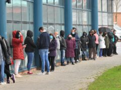 Members of the public queue for a Covid-19 test at Rhydycar leisure centre in Merthyr Tydfil (Ben Birchall/PA)