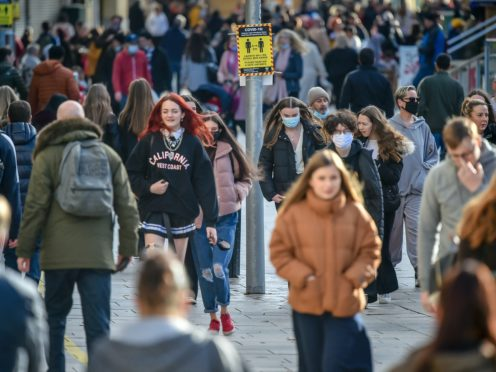 People pass a social distancing sign in Cardiff (Ben Birchall/PA)