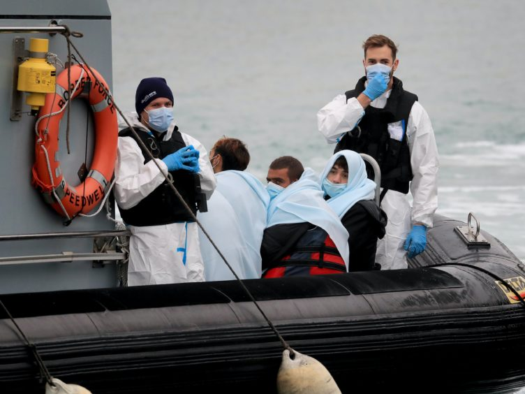 A group of people thought to be migrants are brought into Dover, Kent, onboard a Border Force vessel following a small boat incident in the Channel (Gareth Fuller/PA)