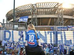 A girl wearing a Maradona number 10 shirt looks at the tributes at Napoli's San Paolo Stadium (Alessandra Tarantino/AP).