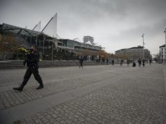 People wait in a queue as police patrol outside of the courthouse in Antwerp, Belgium (Virginia Mayo/AP)