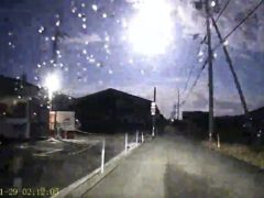 A brightly burning meteor is seen over a road in Japan (Kamio via AP)