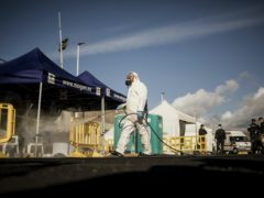 A worker sanitises the area used by migrants at the port on Gran Canaria (Javier Fergo/AP)