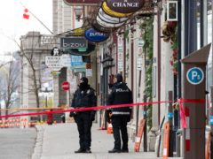 Police officers guard the site of the multiple stabbing (Jacques Boissinot/The Canadian Press via AP/PA)