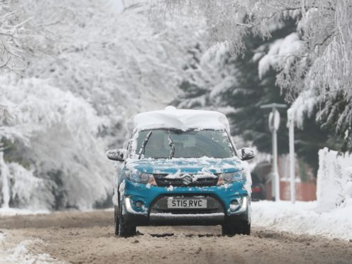 A car is driven along a snow covered road in the Blue Bell Hill area near Maidstone, Kent, after snowfall on Friday and overnight is expected to bring widespread disruption.