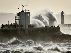 People watch as huge waves hit the sea wall in Porthcawl (Ben Birchall/PA)