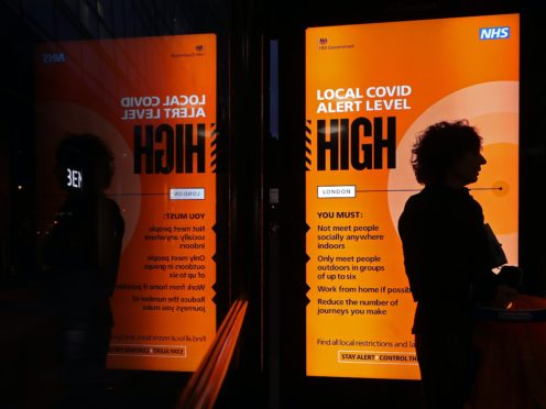 An Covid high alert level sign on a bus shelter in central London (Yui Mok/PA)