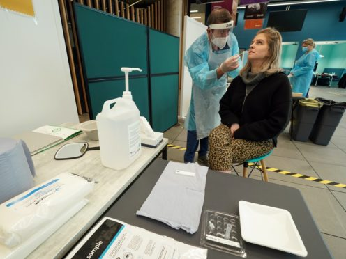 A student, Amy Hariot Ingle, from Newcastle University, is shown how to administer a Covid-19 test (Owen Humphreys/PA)