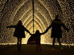 Lulu Kingstone, nine, Alfred Alejandro Dudely-Mira, three, and Elena Kingstone, 11, walk through the Cathedral of Light, a pealight-lit tunnel of lights, during a preview for Christmas at Kew at the Royal Botanic Gardens in Kew, London (Andrew Matthews/PA)