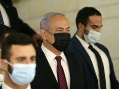 Israeli Prime Minister Benjamin Netanyahu, centre, arrives at the Israeli Knesset for the vote (Alex Kolomoisky/AP)