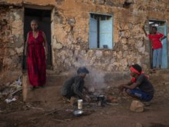 Tigrayans who fled the conflict in Ethiopia's Tigray region, start wood fires to prepare dinner, in front of their temporary shelters at Umm Rakouba refugee camp in Qadarif, eastern Sudan (Nariman El-Mofty/AP)