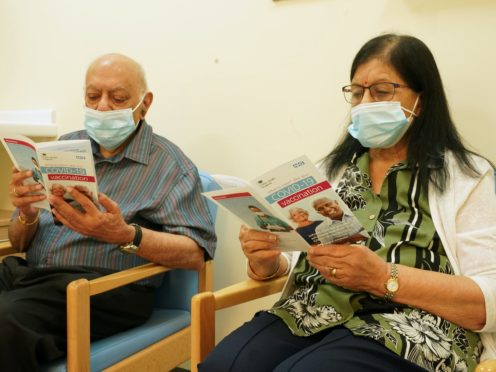 Dr Hari Shukla, 87, and his wife Ranjan read vaccination information leaflets before receiving the first of two Pfizer/BioNTech Covid-19 vaccine jabs (Owen Humphreys/PA)