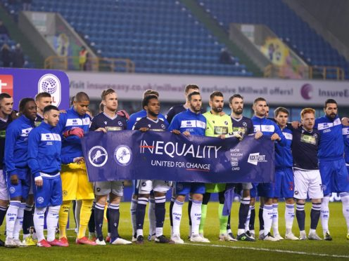 Millwall and QPR players held up an anti-racism banner before their Championship game at The Den (John Walton/PA)