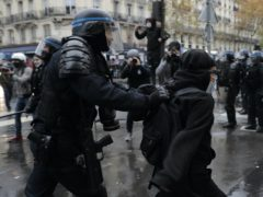 A riot police officer detain a protester during the demonstration in Paris (Lewis Joly/AP)