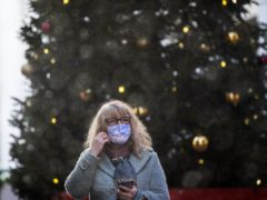 A woman wearing a face mask in front of a Christmas tree in the Leadenhall Market in London .