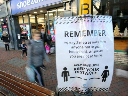 People walk past a Covid-19 notice in Ashford, Kent (Gareth Fuller/PA)