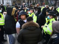 Police talk with demonstrators during an anti-lockdown protest in Parliament Square (Kirsty O'Connor/PA)