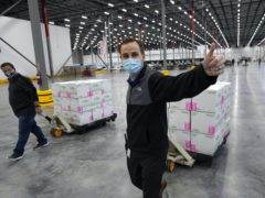 A worker gives a thumbs up while transporting boxes containing the Moderna Covid-19 vaccine to the loading dock for shipping (Paul Sancya, Pool/AP)