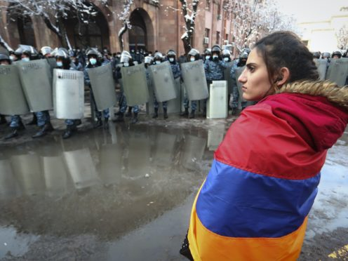 A woman wearing a state Armenian flag stands in front of a riot police line (Vahram Baghdasaryan/AP)