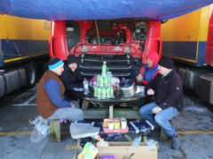 Polish lorry drivers with a makeshift Christmas tree fashioned out of empty Heineken cans, share Christmas Day food and drinks at a truck stop near Folkestone, Kent (Gareth Fuller/PA)