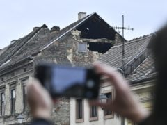 A resident takes a photograph of the damage caused by an earthquake in Sisak, Croatia (AP)