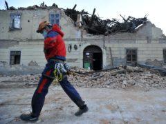 A rescuer walks past a building damaged in an earthquake in Petrinja, Croatia (AP)