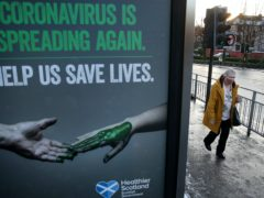 A person wearing a face covering walks passed a coronavirus-related poster (Andrew Milligan/PA)
