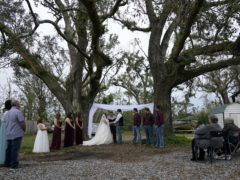Emily and Taylor Pascale exchange their wedding vows outside the home of Taylor's parents in Grand Lake, Louisiana, which was heavily damaged from hurricanes Laura and Delta (Gerald Herbert/AP)