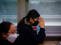 A student wearing a face mask prays before the start of the annual university entrance examination amid the coronavirus pandemic at an exam hall in Seoul, South Korea (Kim Hong-Ji/AP)