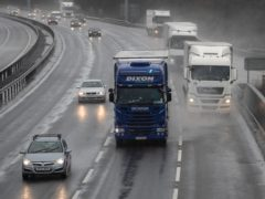Cars travel along the M1 motorway through wet and windy weather.