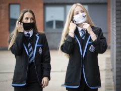 Leah McCallum (left) and Rebecca Ross, S4 students at St Columba's High School, Gourock, put on their protective face masks as the requirement for secondary school pupils to wear face coverings when moving around school comes into effect from today across Scotland.
