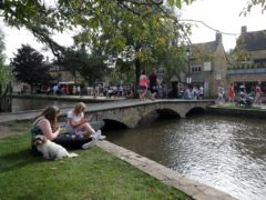 People enjoy the warm weather at Bourton-on-the-Water in the Cotswolds in 2020 (David Davies/PA)