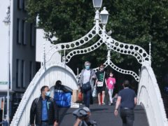 People wearing masks crossing the Ha'penny Bridge in Dublin city centre (Niall Carson/PA)