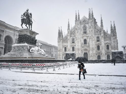 A woman walks in front of the Duomo cathedral in Milan, Italy (Claudio Furlan/LaPresse via AP)