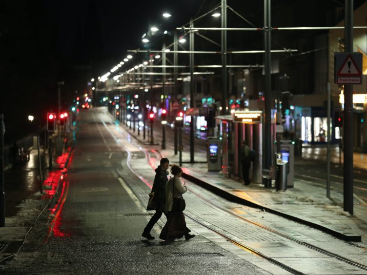 A couple walk through a quiet Princes Street in Edinburgh as people were urged to avoid Hogmanay celebrations (Andrew Milligan/PA)