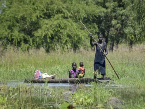 A mother holds her baby as she is transported by dugout canoe through floodwaters in the village of Wang Chot, Old Fangak county, Jonglei state, South Sudan (Maura Ajak/AP)