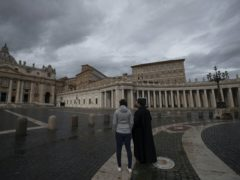 Two people stand in an empty St Peter's Square, at the Vatican as Pope Francis recites the Angelus noon prayer in his studio (Alessandra Tarantino/AP)
