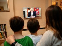 A family in Knutsford, Cheshire, watch Prime Minister Boris Johnson making a televised address (Martin Rickett/PA)