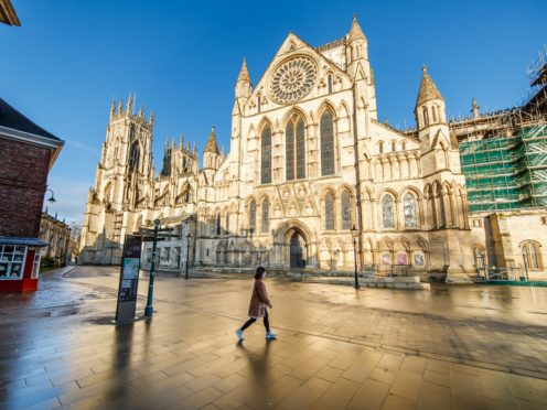 A woman walks past York Minster in Yorkshire the day after Prime Minister Boris Johnson ordered a new national lockdown for England (Danny Lawson/PA)