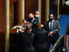 US Capitol Police with guns drawn stand near a barricaded door as protesters try to break into the House Chamber at the US Capitol (Andrew Harnik/AP)