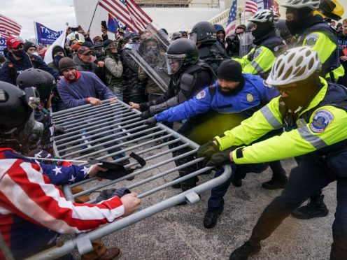Trump supporters try to break through a police barrier (John Minchillo/AP)