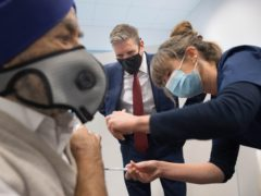 Labour leader Sir Keir Starmer watches as Dr Lizzie Goodman injects a patient with their first dose of the Pfizer-BioNTech COVID-19 Vaccine at the Sir Ludwig Guttman Health and Wellbeing Centre in Stratford, east London (Stefan Rousseau/PA)