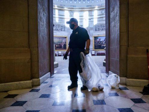 A workman cleans up debris outside the office of Speaker of the House Nancy Pelosi (J. Scott Applewhite/AP)