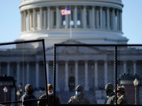With the US Capitol in the background, authorities stand behind newly placed fencing (Evan Vucci/AP)