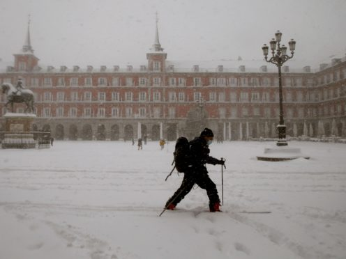 A man skis while crossing the Plaza Mayor during a heavy snowfall in Madrid, Spain, Saturday, Jan. 9, 2021. An unusual and persistent blizzard has blanketed large parts of Spain with snow, freezing traffic and leaving thousands trapped in cars or in train stations and airports that had suspended all services as the snow kept falling on Saturday. The capital, Madrid, and other parts of central Spain activated for the first time its red weather alert, its highest, and called in the military to rescue people from cars vehicles trapped in everything from small roads to the city's major thoroughfares. (AP Photo/Andrea Comas)