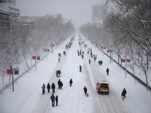 People walk along El Paseo de la Castellana avenue during a heavy snowfall in Madrid (AP)