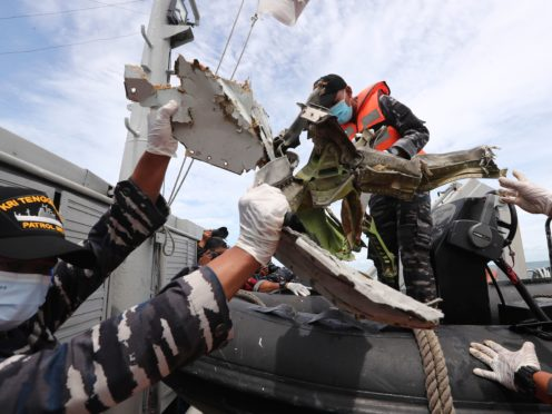 Indonesian navy personnel remove a part of aircraft recovered in the Java Sea where a Sriwijaya Air passenger jet crashed near Jakarta, Indonesia (Tatan Syuflana/AP)